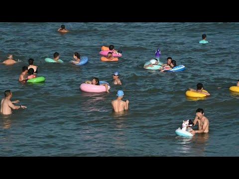 روّاد شاطئ صيني يُزيّنون مياهه بالعوامات الملونة